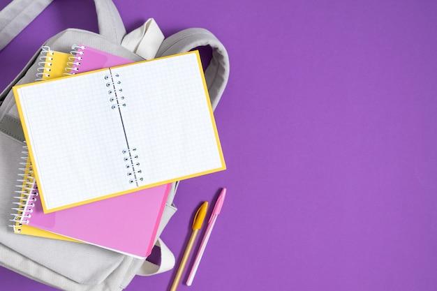 Rucksack mit bunten schulmaterialien auf lila hintergrund zurück zur schule flache draufsicht cop