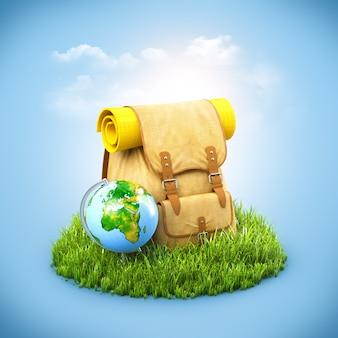 Rucksack mit globus auf gras