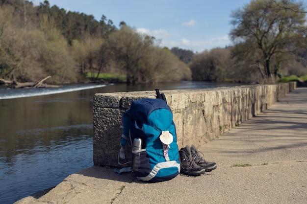 Rucksack mit muschelsymbol des jakobswegs, trekkingstiefeln und stöcken an der steinmauer