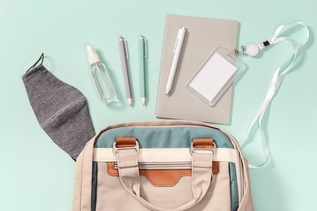 Rucksack mit schulmaterial, gesichtsmaske und händedesinfektionsmittel, schülerabzeichen, hefte, stifte