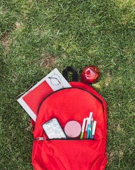 Rucksack mit schulmaterial und apfel