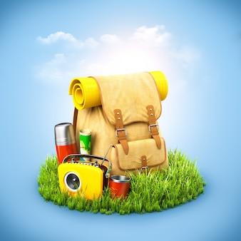 Rucksack mit termokarte und radio auf gras