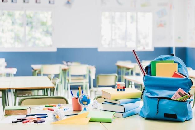 Rucksack und gestapelte bücher auf schreibtisch im leeren klassenzimmer