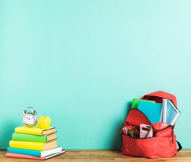 Rucksack und lehrbücher auf dem schreibtisch