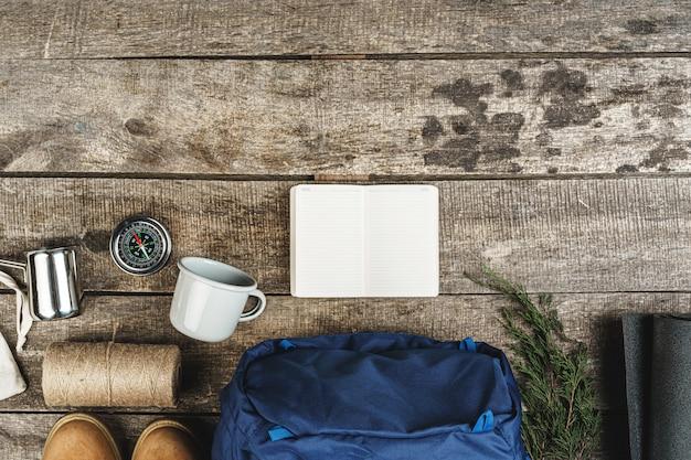 Rucksack und wanderausrüstung auf holztisch, draufsicht