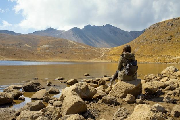 Rucksackfrau, die vulkankraterlandschaft in mexiko beobachtet