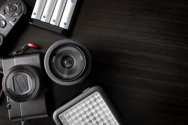 Rucksackreise- und fotografenkonzept auf holzhintergrund mit objektiv, kamera, fernauslöser