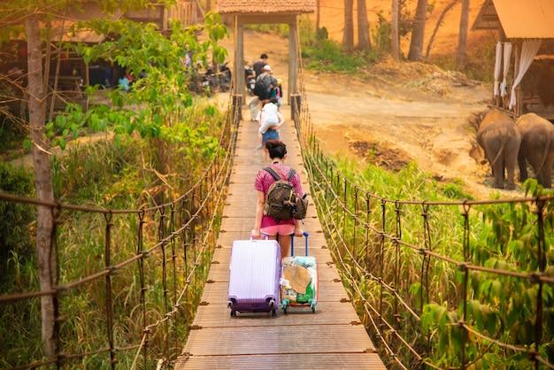 Rucksackreisend-sommerreise, die über holzbrücke geht