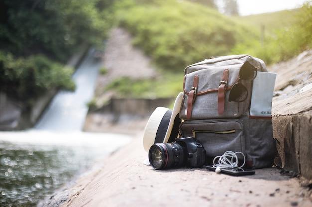 Rucksackreiseweinlese mit tasche, kamera, karte, hut, kopfhörer und mobiltelefon auf boden im sommertageswasserfallhintergrund. abenteuerreisen.