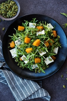 Rucola, blauschimmelkäse, kürbis, kürbiskerne, salat in einem teller, draufsicht