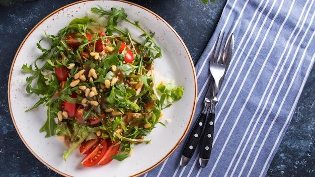 Rucola mit pinienkernen, tomaten und käse. gesunder frischer salat mit rucola. draufsicht. speicherplatz kopieren