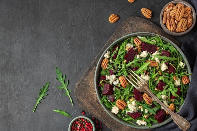 Rucola-, rüben- und blauschimmelkäsesalat mit pekannüssen in einem teller mit gabel auf schwarzem tisch