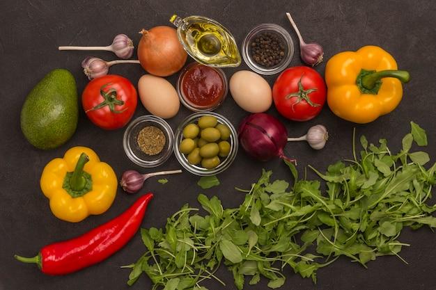 Rucola und spinat, eier und tomaten, paprika, knoblauch, oliven auf schwarzem hintergrund