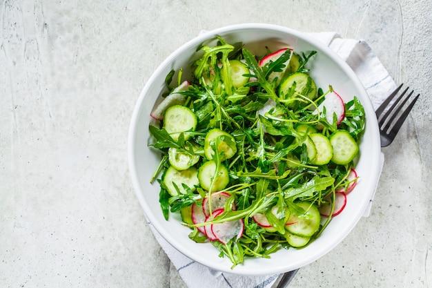 Rucolasalat mit gurke und rettich. gesundes lebensmittelkonzept.