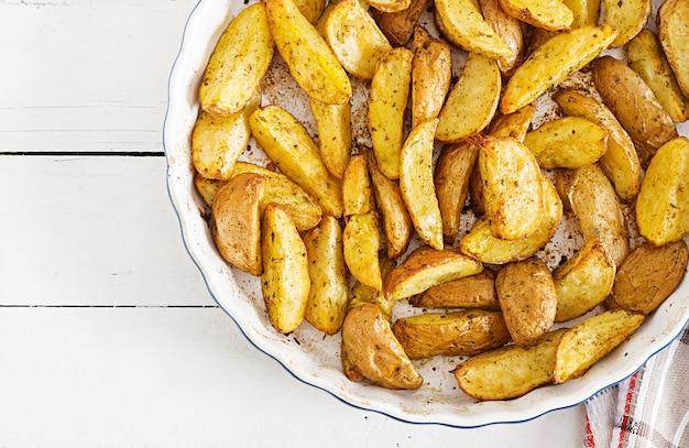 Ruddy baked potato-keile mit knoblauch auf einer weißen tabelle. flach liegen. ansicht von oben.