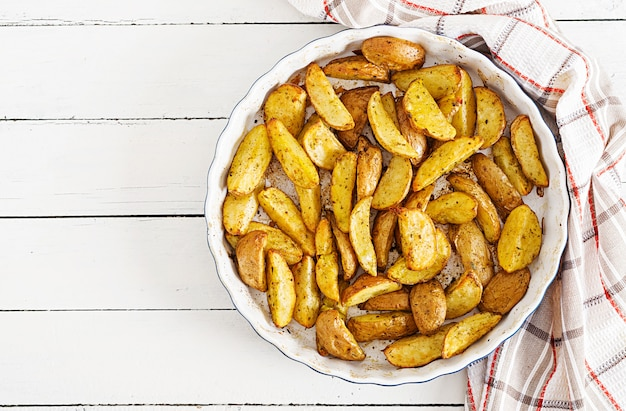 Ruddy baked potato wedges mit knoblauch auf einem weißen hintergrund.