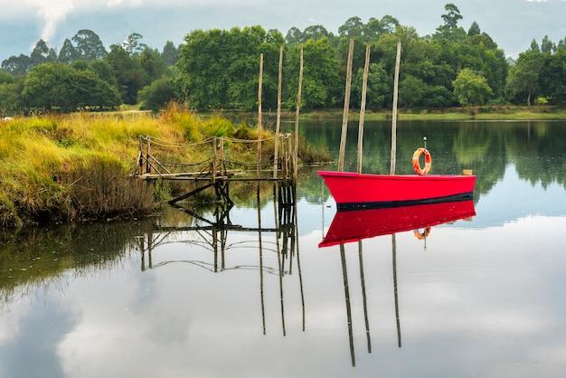 Rudimentärer holzsteg mit rotem boot auf dem fluss mit ruhigem wasser.