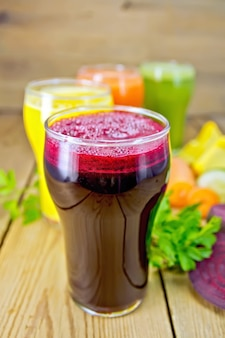 Rübensaft im vordergrund und karottensaft, kürbis und gurke in einem hohen glas, gemüse auf einem holzbretthintergrund