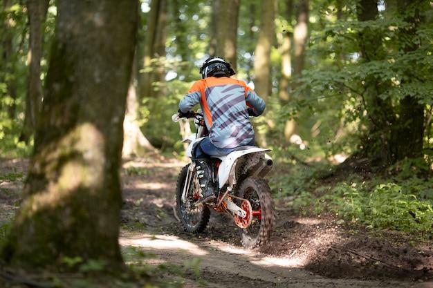 Rückansicht aktiver mann, der motorrad im wald reitet