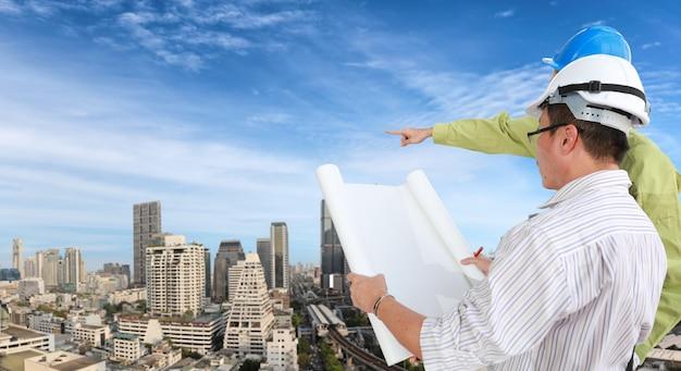 Rückansicht architektenmänner stehen und prüfen konstruktionszeichnungen mit bauarbeiterhelm. asiatischer geschäftsleiter und arbeiter, die in zukunft mit gebäude- und stadtbildhintergrund suchen.