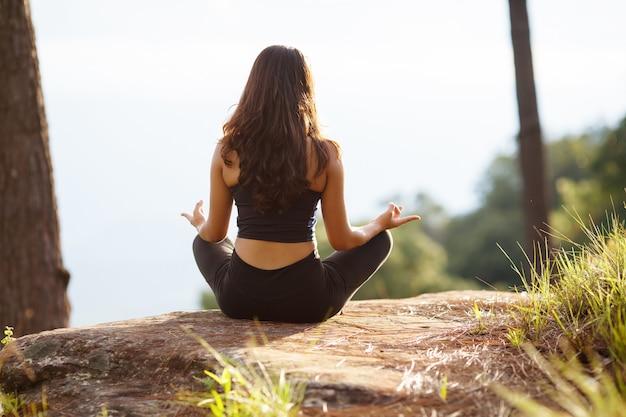 Rückansicht asiatische frau beim yoga am berg