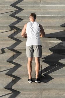 Rückansicht athletischer mann, der liegestütze auf treppen tut