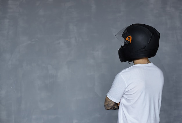 Rückansicht auf biker im schwarzen helm und im weißen t-shirt