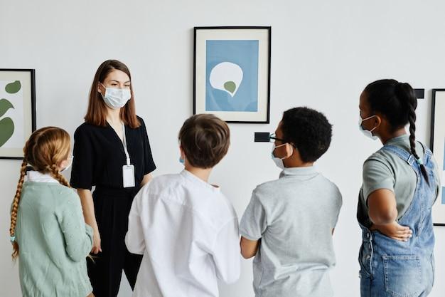 Rückansicht auf verschiedene gruppen von kindern, die gemälde in der kunstgalerie mit einer lehrerin mit maske betrachten