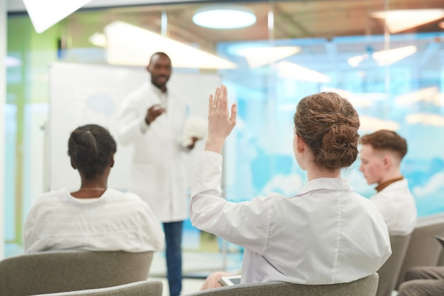 Rückansicht bei jungen leuten, die hände heben, während sie dem medizinischen seminar im college zuhören, platz kopieren