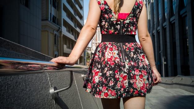 Rückansicht bild einer sexy frau im kurzen kleid, die hand am metallgeländer hält, während sie auf der straße geht
