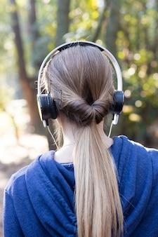 Rückansicht blonde frau, die musik in den wald zu hören