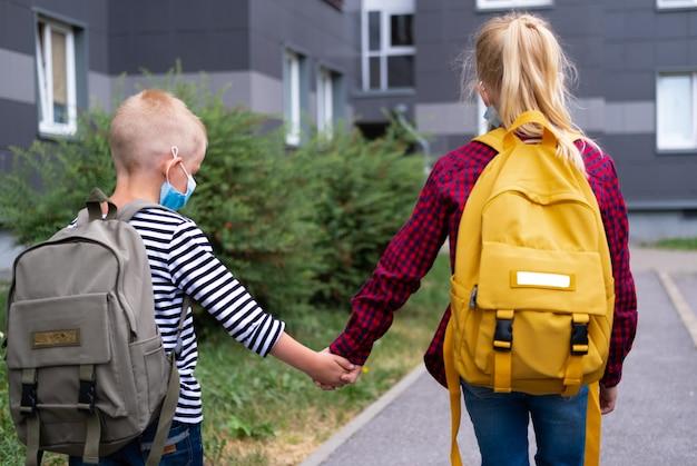 Rückansicht bruder und schwester gehen nach der pandemie zur schule. kinder, die maske und rucksäcke tragen, schützen und schützen vor coronavirus für den schulanfang.