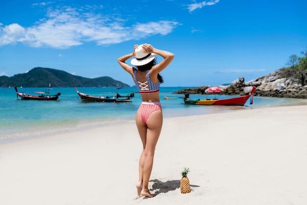 Rückansicht: das perfekte mädchen posiert am strand. der reise. schönes weibliches modell mit tropischer frucht nahe mit ihr. thailändische boote auf