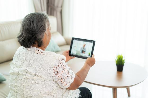 Rückansicht der älteren frau, die videoanruf mit ihrem arzt mit ihrem gefühl krank macht