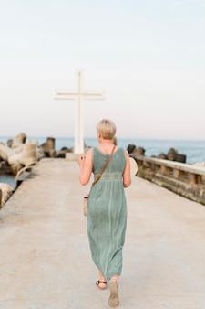 Rückansicht der älteren touristenfrau, die ihre zeit am strand genießt