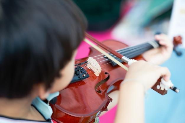 Rückansicht der aktion des jungen spielt geige auf unschärfennotenhintergrund, selektiver fokus