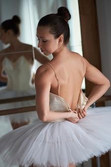 Rückansicht der anmutigen ballerina, die ihr kostüm aufknöpft.
