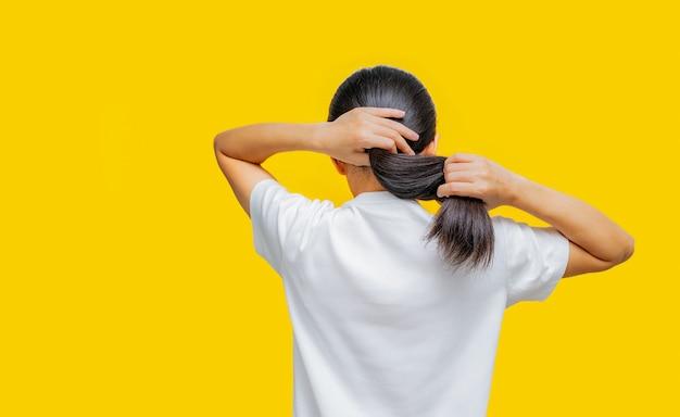 Rückansicht der asiatin, die beschädigtes haar auf gelbem hintergrund mit kopienraum hält. spliss haarproblem bei der frau. trockenes und sprödes schwarzes langes haar braucht shampoo und spülung für die spa-behandlung.