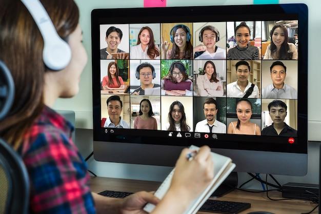 Rückansicht der asiatischen geschäftsfrau bei der arbeit und online-meeting per videokonferenz mit kollegen
