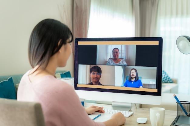 Rückansicht der asiatischen geschäftsfrau, die mit ihren kollegen über plan in videokonferenz spricht.