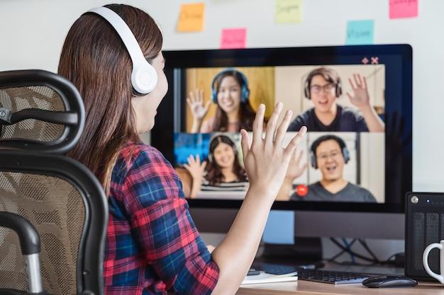 Rückansicht der asiatischen geschäftsfrau sagt hallo mit teamwork-kollegin in videokonferenz