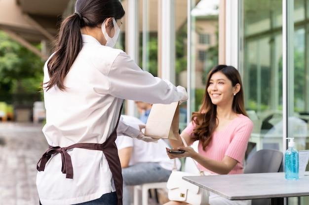 Rückansicht der asiatischen kellnerin mit gesichtsmaske geben bestellung des herausnehmenden nahrungsmittelbeutels zur attraktiven weiblichen kundin. food-service-konzept zum mitnehmen oder zum mitnehmen nach einer coronavirus-pandemie.