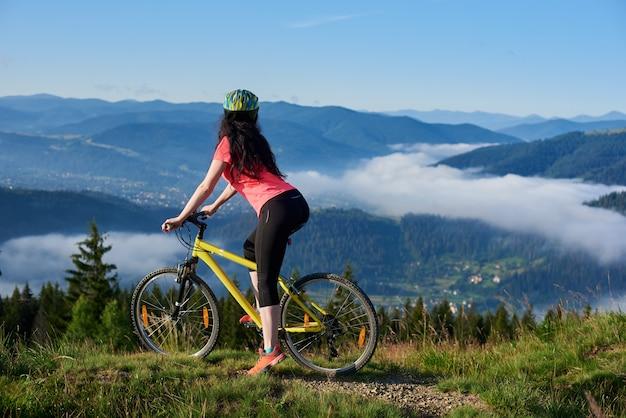 Rückansicht der attraktiven bikerin, die auf gelbem fahrrad auf der bergspitze am morgen fährt. neblige berge, wälder auf dem unscharfen hintergrund
