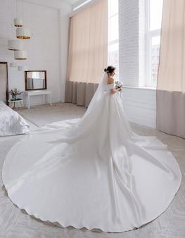 Rückansicht der attraktiven braut gekleidet im luxushochzeitskleid, das im raum neben dem fenster steht