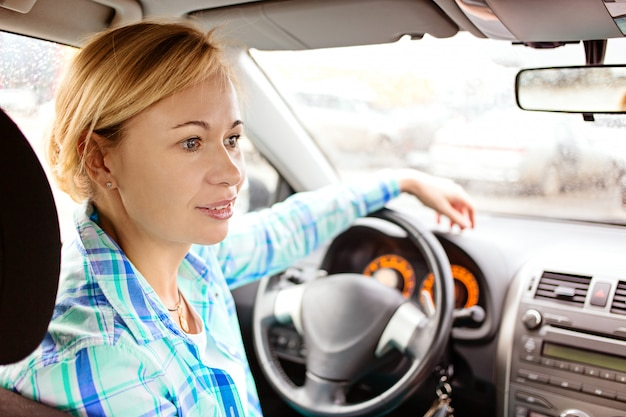 Rückansicht der attraktiven frau in der freizeitkleidung, die über ihre schulter schaut, während sie ein auto fährt