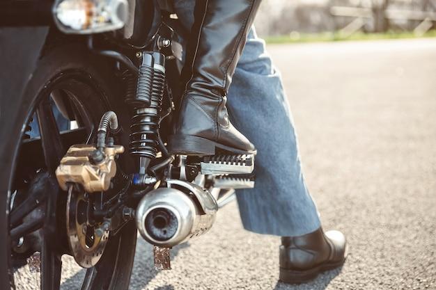 Rückansicht der beine eines älteren paares mit stiefeln, die über dem motorrad sitzen, bereit zu gehen