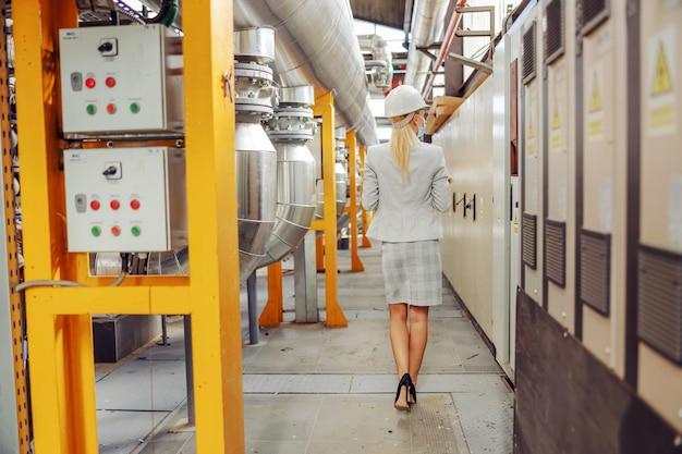 Rückansicht der blonden geschäftsfrau im anzug, mit schutzmaske, mit helm auf kopf, der durch heizwerk geht.