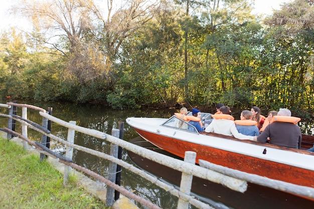 Rückansicht der familie auf dem boot neben einem holzzäune