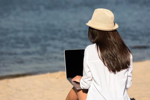 Rückansicht der frau am strand mit laptop