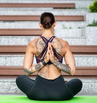 Rückansicht der frau, die beim yoga meditiert
